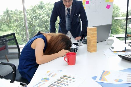 Angry boss looking afraid stressed tired employee in workplace of office.