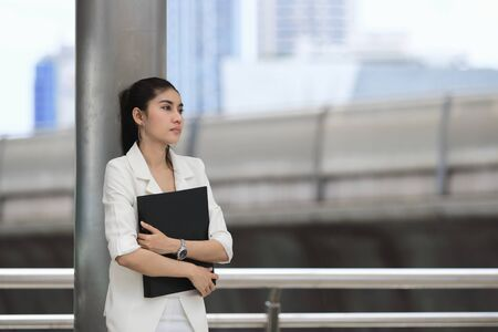 Stressed young Asian business woman with document folder standing at outside office.