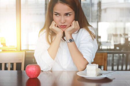 Selective focus on face of frustrated stressed Asian woman choosing between apple or unhealthy cake on the desk with sunshine effect. Healthy lifestyle and dieting concept.