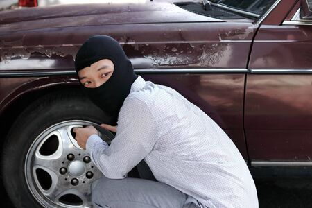 Masked thief in black balaclava trying to break into car. Criminal crime concept. 写真素材