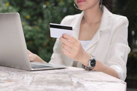 Attractive young Asian woman with laptop and credit card for shopping online.