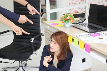 Depressed stressed young Asian business woman with fingers pointing at her in workplace of office. 写真素材