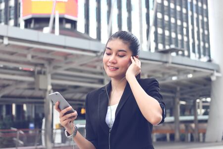 Relaxed young Asian woman listening music with mobile smart phone in urban city.