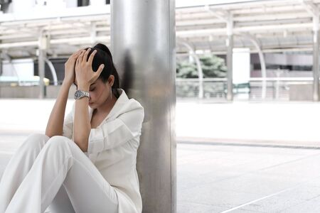 Frustrated stressed young Asian business woman with hands on face sitting at outdoors. 写真素材