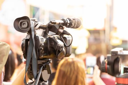 Professional digital video camera technician. Videographer with equipment at event.