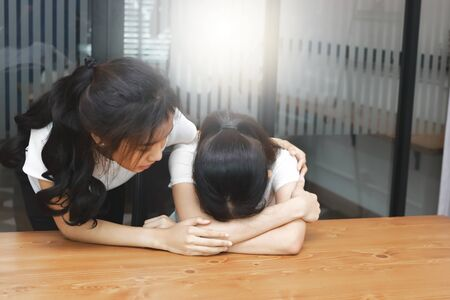 Young Asian woman comforting her depressed friend in living room.