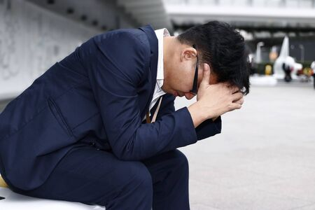 Unemployed stressed young Asian business man suffering from severe depression. Failure and layoff concept.