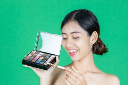 Beauty face of young Asian woman applying make up with brush over green isolated background. Healthy and cosmetics concept.
