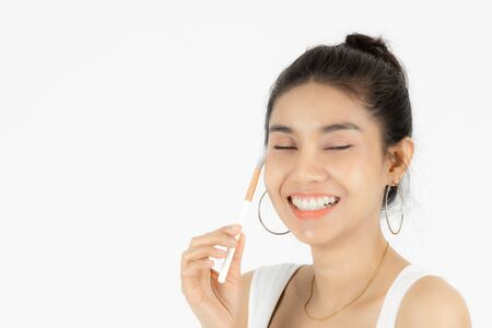 Beauty face of young Asian woman applying make up with brush over white isolated background. Healthy and cosmetics concept.