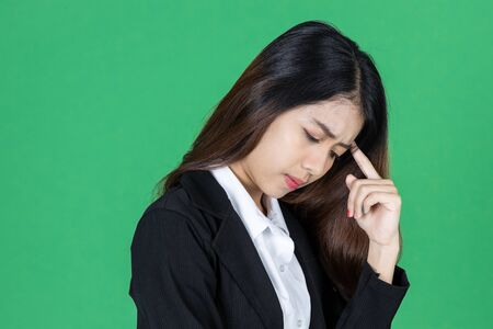 Frustrated stressed young Asian business woman with hands on face in depression on green isolated background.