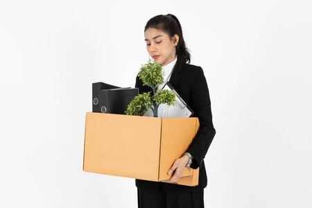 Fired unemployed young Asian business woman in suit holding box with personal belongings on white isolated background. Unemployment, failure and layoff concept.