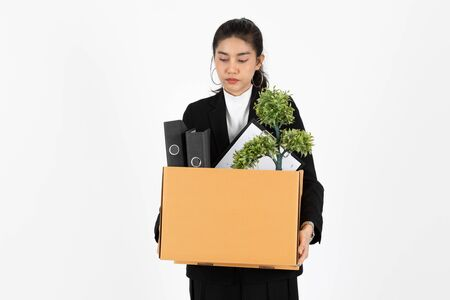 Fired dismissal young Asian business woman in suit holding box with personal belongings on white isolated background. Unemployment, failure and layoff concept.
