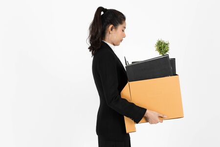 Side view of fired dismissal unemployed young Asian business woman in suit holding box with personal belongings on white isolated background. Unemployment, failure and layoff concept.