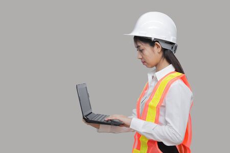 Beauty confident young Asian worker with safty equipment carrying laptop on gray isolated background.