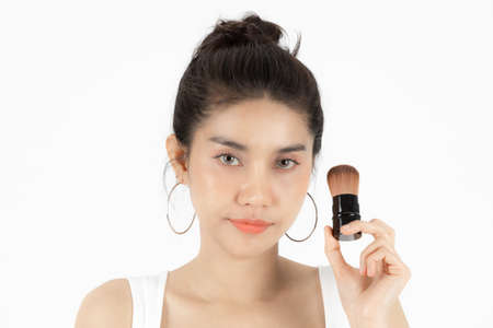 Healthy and cosmetics concept. Beauty face of young Asian woman applying make up with brush over white isolated background.