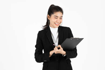 Portrait of confident young Asian business woman holding document folder or ring binder posing over white isolated background. Foto de archivo
