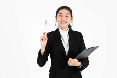 Portrait of attractive young Asian business woman holding pen and having idea posing over white isolated background. Foto de archivo