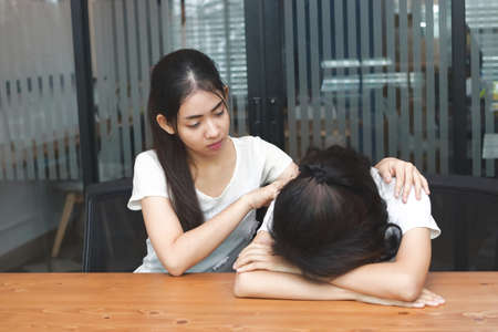 Asian woman comforting to sad depressed friend. Young woman consoling sad girl at home. Friendship and people concept.