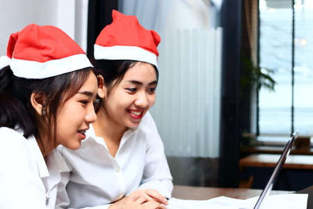 Smiling young Asian women with santa claus hat shopping online together in christmas holiday. Happiness in holidays concept.