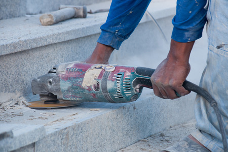 close up shot of working electric grinding machine on marble stone