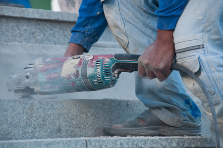 close up shot of working electric grinding machine on marble stone photo