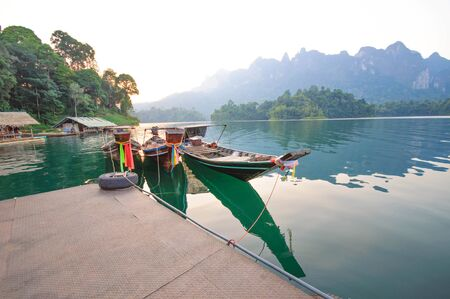 sok: Long-tail boat and lakeside raft houses on Cheow Lan Lake, Khao Sok National Park in southern Thailand