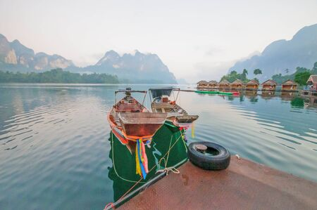 Long-tail boat and lakeside raft houses on Cheow Lan Lake, Khao Sok National Park in southern Thailand photo