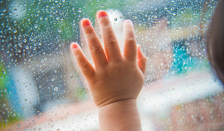 vehicle window: Rain drops on the car window and children hand . Abstract background