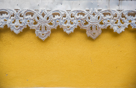 perforated pattern metal plate on yellow wall