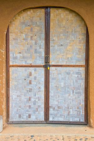 berm: Bamboo wickerwork door of a vintage cob house in Northern Thailand Stock Photo