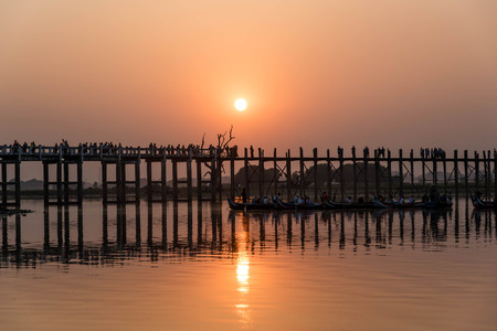 silhouetted: Silhouetted on U Bein Bridge at sunset, Amarapura, Mandalay region, Myanmar Stock Photo