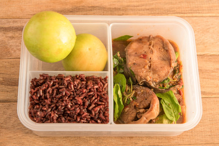 boxed: Spicy stir-fried catfish with basil served with riceberry rice in lunch box,bento box,Thai styled food.