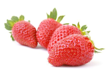 Four fresh strawberries isolated on white background.