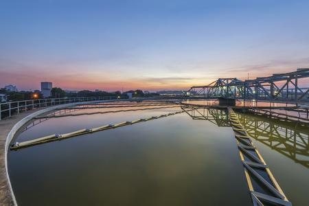 cuenca de sedimentación, aguas residuales fluye a través de grandes tanques Foto de archivo