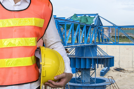 water treatment plant: engineering man with yellow safety helmet standing in front of water treatment plant