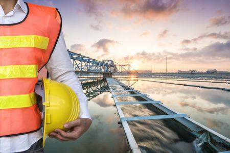 aguas residuales: Ingeniero con el sólido Tipo de contacto del tanque clarificador proceso de recirculación de fangos en la Planta de Tratamiento de Agua con Sun Rise Foto de archivo