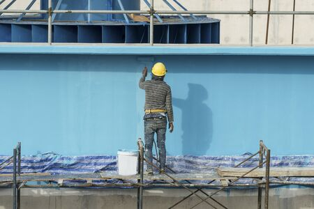 outside house: painting facade builder worker movement with roller at Water Treatment Plant Stock Photo
