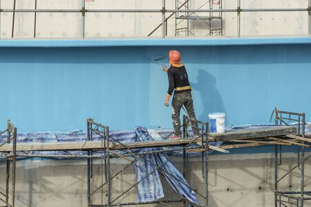 steeplejack: painting facade builder worker movement with roller at Water Treatment Plant Stock Photo