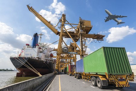 Industrial Container Cargo freight ship with working crane bridge in shipyard at port