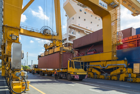 Container Cargo freight ship with working crane loading bridge in shipyard with Logistic Import Export background