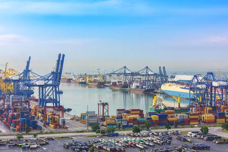 ロジスティックのインポートおよびエクスポートの背景の夕暮れ時に造船所のクレーン橋を扱うコンテナー貨物船します。