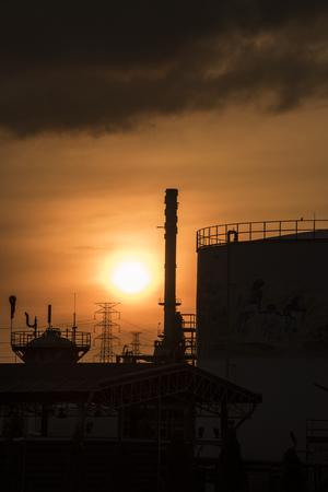 siluate van grote olietanks in een raffinaderij met zonsopgang