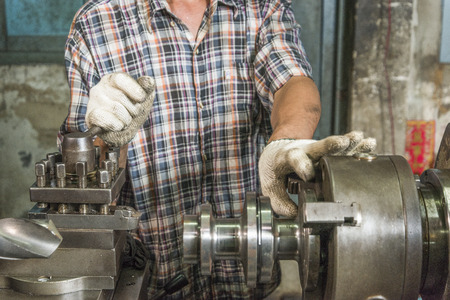 arbeider check meting een deel van het werk in een staal machine winkel