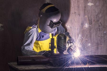 welding mask: Worker welding the steel part by manual Stock Photo