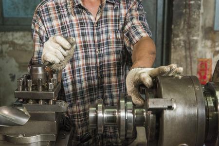 Werknemer controleren meet een deel van het werk in een stalen machine winkel Stockfoto