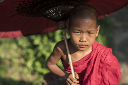buddhist's: Young Buddhist monk with umbrella at monastery, Myanmar