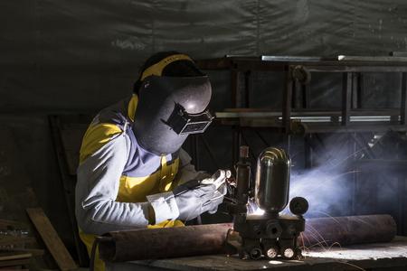 Worker welding the steel part by manual Foto de archivo