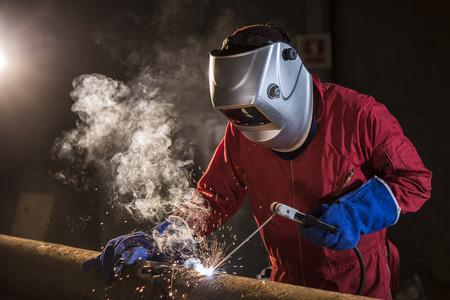Pracownik spawanie rurociągu w obszarze budownictwa Zdjęcie Seryjne