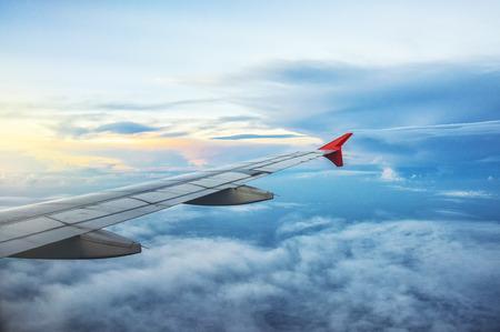 Vleugel van een vliegtuig dat boven de wolken in schemering vliegt