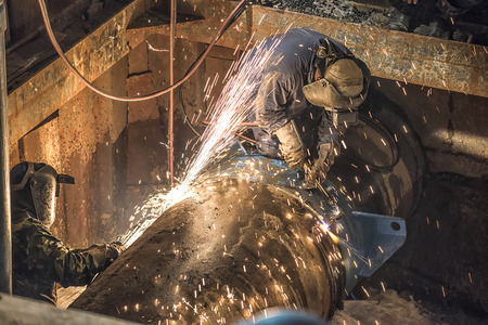 worker welding pipleine in a pipeline construction